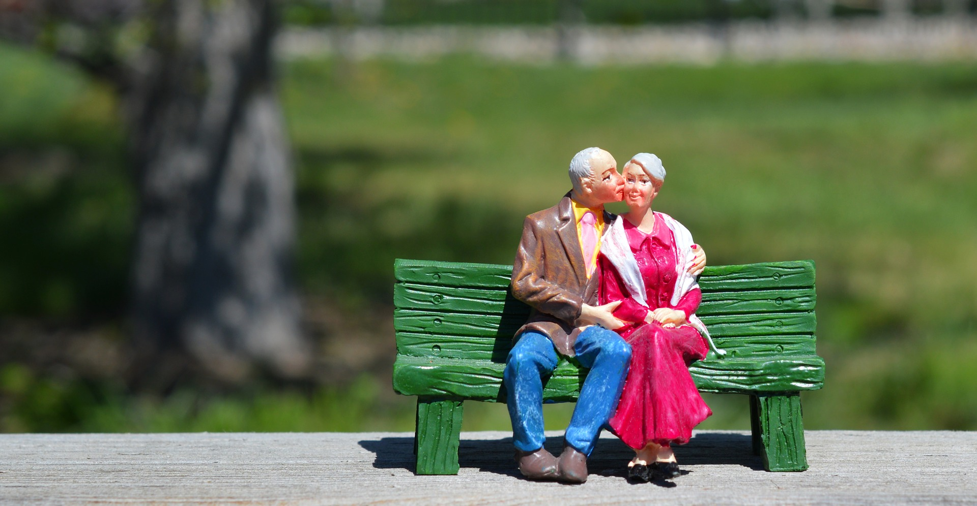 old couple in a bench figurine retirement training paradigm