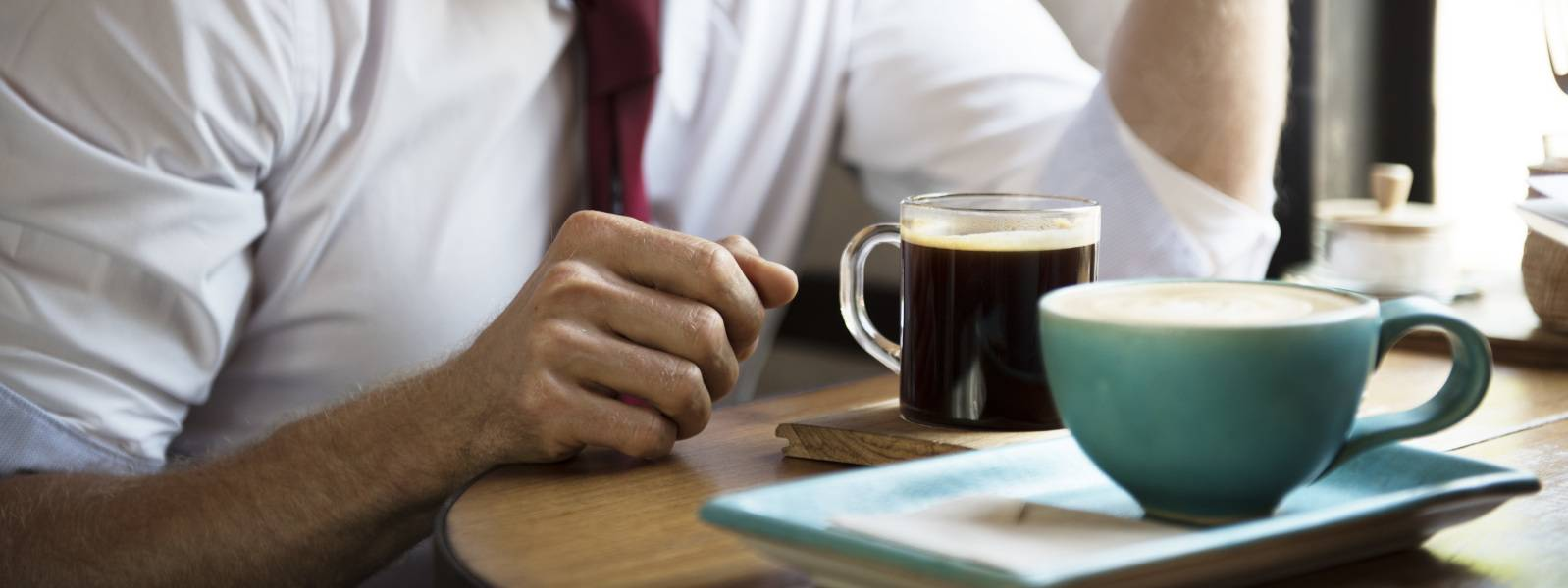 businessman drinking coffee mug high amounts of caffeine exacerbate sleep deprivation
